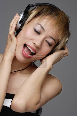 woman with headphones on listens to music