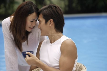 couple touching foreheads poolside
