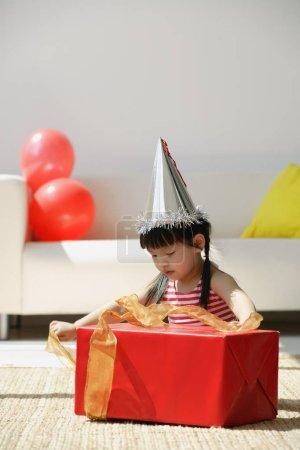 girl unwraps a birthday present