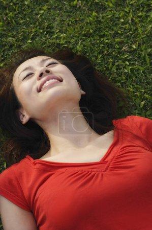 Photo pour Femme souriante, allongée sur l'herbe - image libre de droit