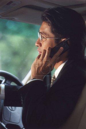 Photo pour Homme cadre parlant sur téléphone cellulaire dans la voiture, profil - image libre de droit