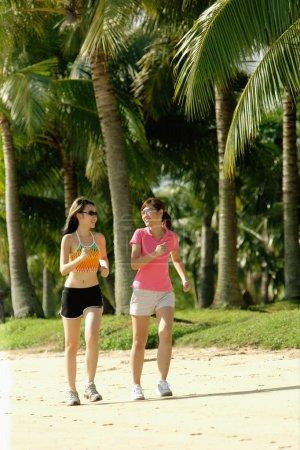 Women jogging along beach