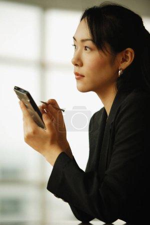 Photo pour Jeune femme assise au bureau, utilisant PDA - image libre de droit