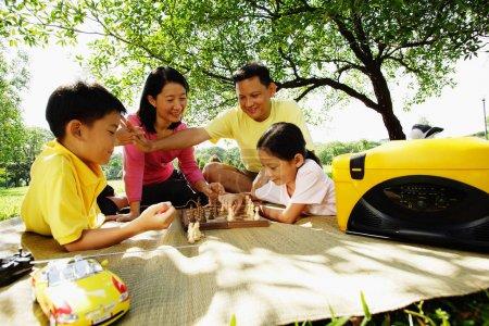 Family playing chess, sitting on picnic mat