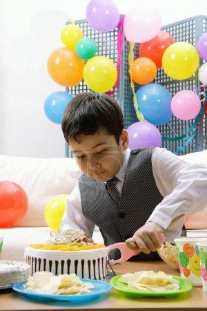 Photo pour Garçon coupe gâteau d'anniversaire - image libre de droit