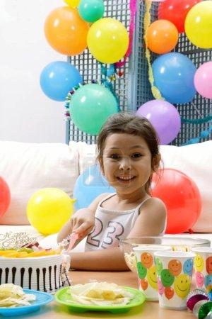 Photo pour Fille coupe gâteau d'anniversaire, regardant la caméra - image libre de droit