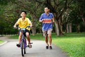 Father teaching son to cycle