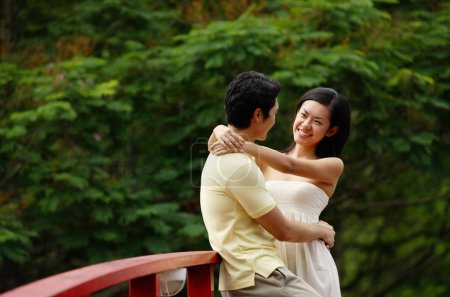 Couple standing face to face on bridge