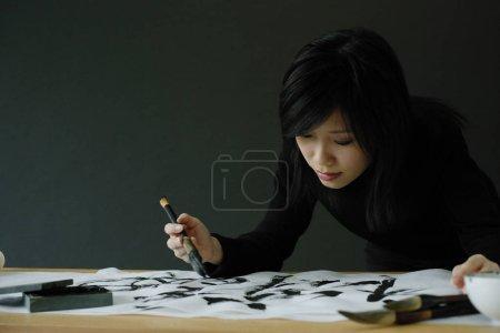 Girl writing Chinese calligraphy