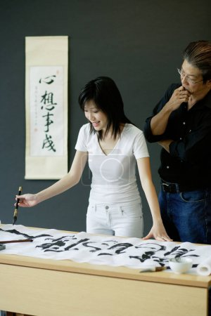 Man and woman writing Chinese calligraphy