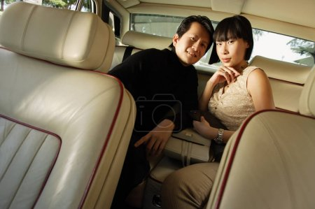 Couple sitting in backseat of car