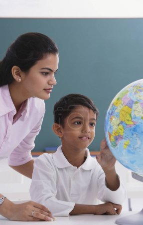 Teacher and student look at globe...