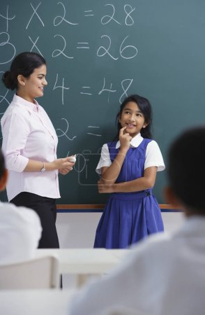 teacher and girl at chalkboard