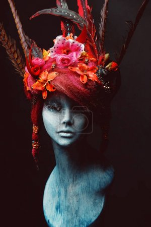 Mannequin in creative headwear with flowers and feathers against dark background