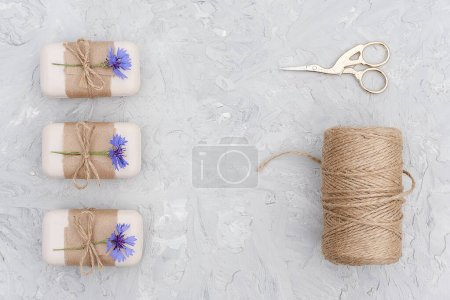 Photo pour Natural handmade soap, decorated kraft paper , blue flower, skein of twine and scissors. Concept of organic cosmetics. Top view Flat lay Copy space Template for design. - image libre de droit