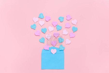 Photo pour Coeurs colorés avec texte AMOUR, Baiser, TOUJOURS VOUS volent sous la forme de coeur de l'enveloppe en papier bleu sur fond rose. Concept de Saint Valentin. Cadeau pour amant. amour confession Copier l'espace . - image libre de droit