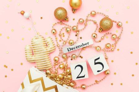 Photo pour Calendrier en bois 25 décembre, cactus noël textile, baubles dorés, étoiles confettis sur fond rose. Joyeux Noël concept. Haut de la page Gabarit plat Modèle pour le design, carte de souhaits, carte postale. - image libre de droit