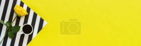 Photo for Cup of coffee and yellow rose on stylish black and white napkin on yellow background. Concept good morning or day. Flat lay Top view Copy space Banner. - Royalty Free Image