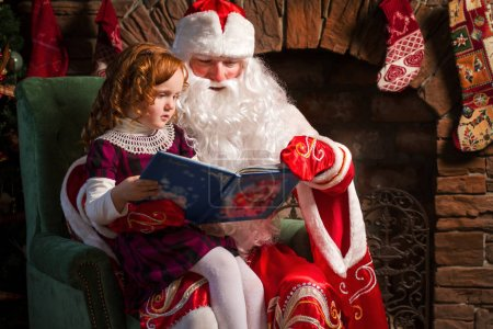 Photo for Santa Claus and little girl reading book against Christmas tree and fireplace - Royalty Free Image