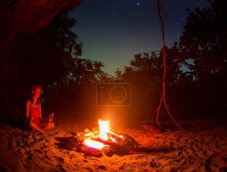 Photo pour Silhouette de fille touristique autour du feu de camp la nuit sur la rive de la rivière - image libre de droit