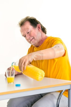 Photo for Middle-aged man with disability pouring natural orange juice from a bottle by using a bionic prosthetic left hand while sitting at a table  with copy space on white. - Royalty Free Image