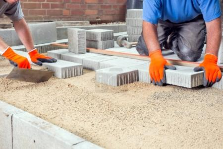 Builders laying paving stones