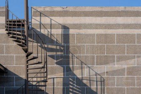 Photo pour Escaliers en acier en spirale circulaires avec décoration légère et ombragée architecture extérieure du bâtiment - image libre de droit