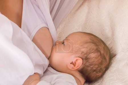 The little child sucks his mother's breast on a bed