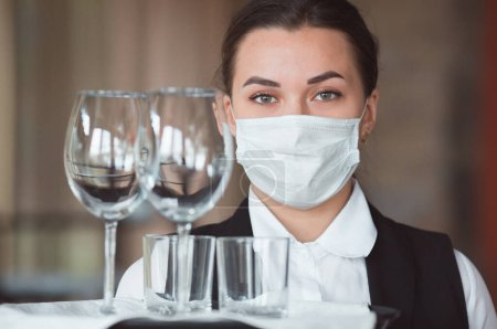 Photo for Work of a waiter in a restaurant in a medical mask - Royalty Free Image