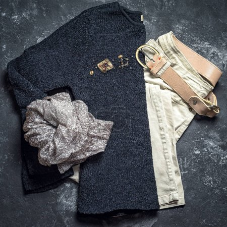 Flat lay top view outfit of casual woman. Black sweater, grey scarf, beige jeans and leather belt on a dark black background.