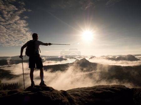 Hiker with backpack reaches the summit of mountain peak. Success, freedom and happiness,