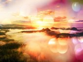 Film effect.  Red daybreak. Misty daybreak in a beautiful hills. Peaks of hills are sticking out from foggy background,