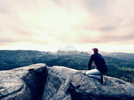 Man tourist sit on peak of mountain. Travel mountain scene. Hiker take a rest  alone on the mountain