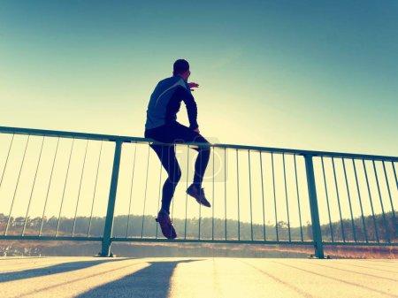 The runner in black leggings makes body stretching on bridge path. Sun outlines man body