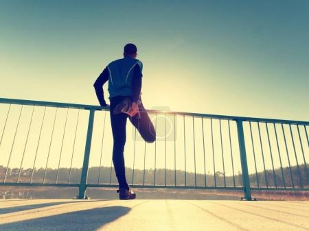 The runner in black leggings makes body stretching on bridge path. Sun outlines man body