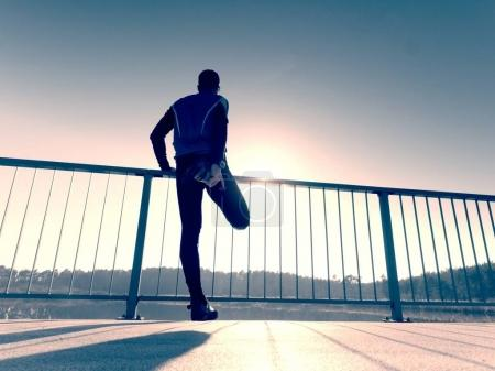 Morning runner in tall black leggings makes body stretching on bridge path. Outdoor exercising