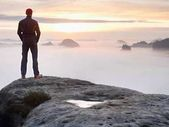 Alone hiker in red cap stand on peak of sandstone rock in rock empires park and watching over the mist
