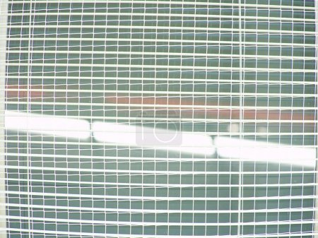 Hall windows secured against breakage by protective net. Industry hall.  Reflections in vacuum glasses