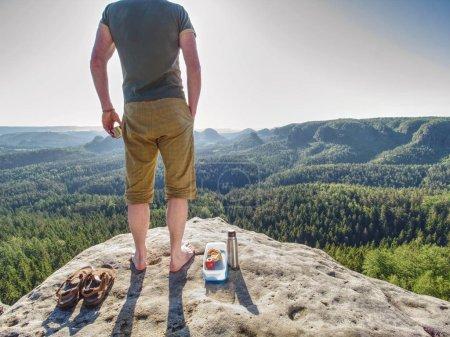 Photo pour Randonneur en shorts et singlet bleu manger des toasts pour le petit déjeuner dans les rochers. Un matin d'été étonnant dans la nature pure. - image libre de droit