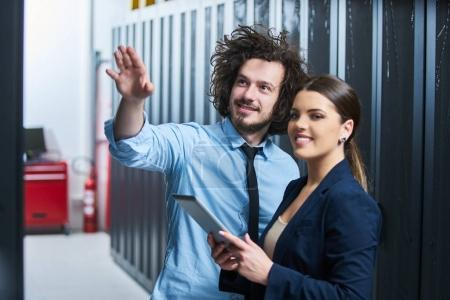 Photo for Two young technicians working at a data center on server maintenance - Royalty Free Image