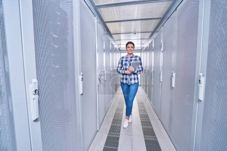 Photo for Female technician working on server maintenance in white server room - Royalty Free Image