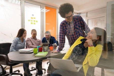 Photo pour Groupe de gens créatifs ayant rencontré un ordinateur portable dans un bureau modern. - image libre de droit