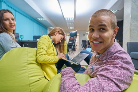 Foto de Retrato de grupo de inicio de gente creativa con una reunión con un ordenador portátil en una oficina moderna. Gente de negocios que relajada conversación sobre el nuevo proyecto en el espacio de coworking - Imagen libre de derechos