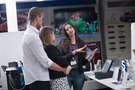 Young couple with a consultant in consumer electronics store