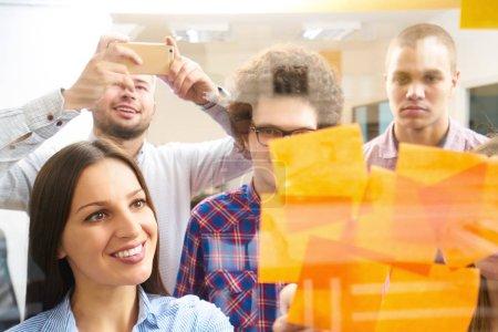 Photo pour Jeunes créateurs d'entreprises en démarrage sur la réunion au bureau moderne faire des plans et des projets avec des autocollants de poste sur le verre - image libre de droit