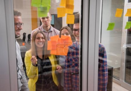 Photo for Young creative startup business people on meeting at modern office making plans and projects with post stickers on glass - Royalty Free Image