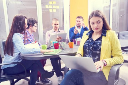 Photo for Portrait of startup group of creative people having a meeting with a laptop in a modern office. Business people having relaxed conversation over new project in coworking space - Royalty Free Image