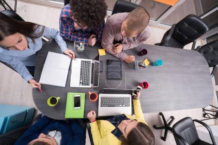 Photo pour Portrait de groupe de démarrage de gens créatifs ayant une rencontre avec un ordinateur portable dans un bureau modern. Gens d'affaires ayant assoupli la conversation sur nouveau projet dans l'espace de coworking - image libre de droit