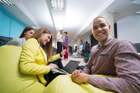 Photo pour Portrait d'un groupe de créateurs en démarrage ayant une réunion avec un ordinateur portable dans un bureau moderne. Les gens d'affaires ayant détendu la conversation sur le nouveau projet dans l'espace de coworking - image libre de droit