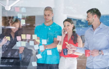 Photo for Business, startup, planning, management and people concept - happy creative team writing on stickers at office glass board - Royalty Free Image